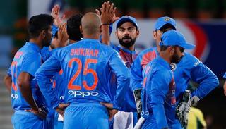 Indian cricketers celebrate the dismissal of Australia's David Warner.