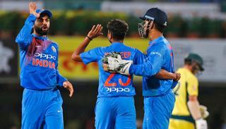 Virat Kohli congratulates Kuldeep Yadav for the wicket of Australia's Aaron Finch .