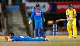 Yuzvendra Chahal lies on the ground after an unsuccessful attempt to take a catch for the dismissal of Australia's Tim Paine.