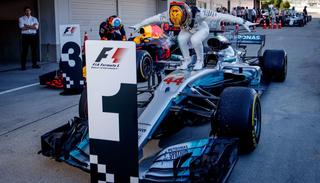Mercedes driver Lewis Hamilton of Britain stands on his car as he celebrates after winning the Japanese Formula One Grand Prix at Suzuka.
