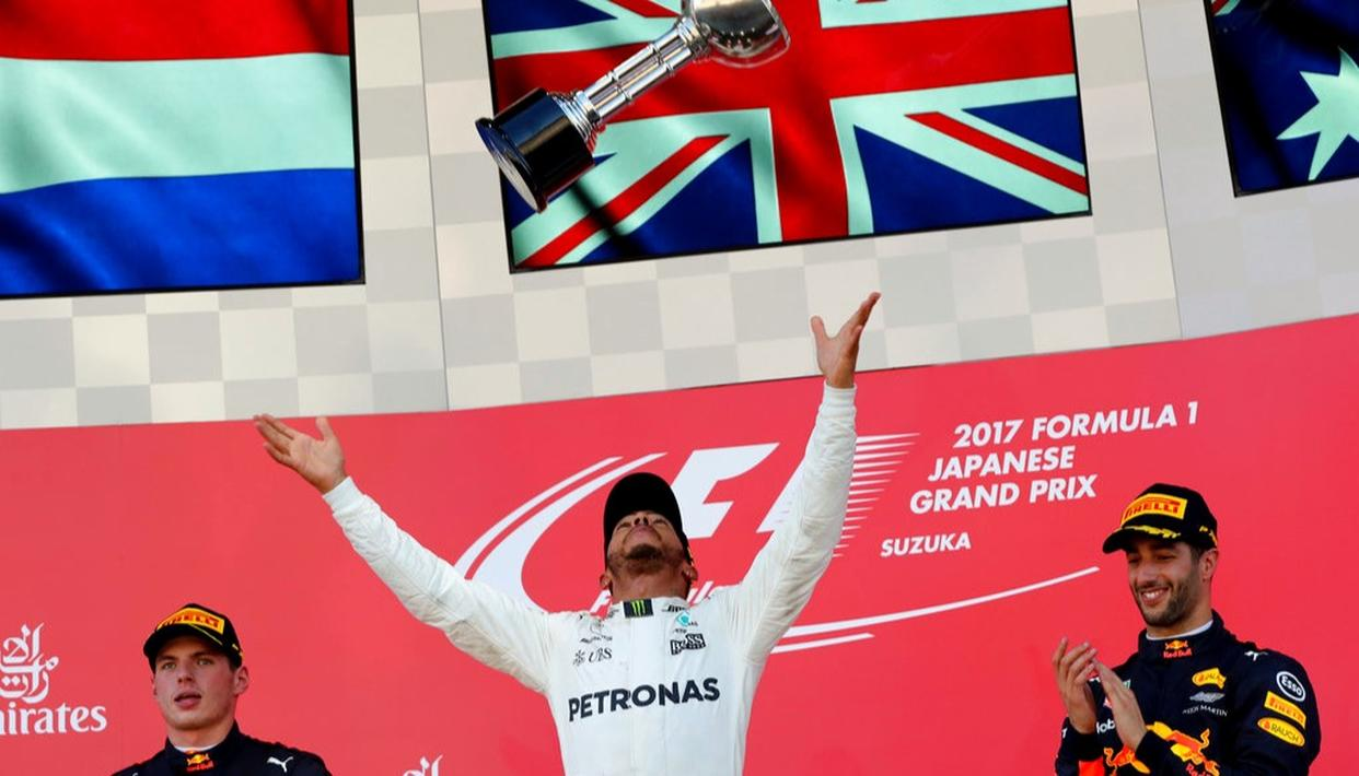 Mercedes driver Lewis Hamilton of Britain throws his trophy aloft as he celebrates after winning the Japanese Grand Prix at Suzuka.