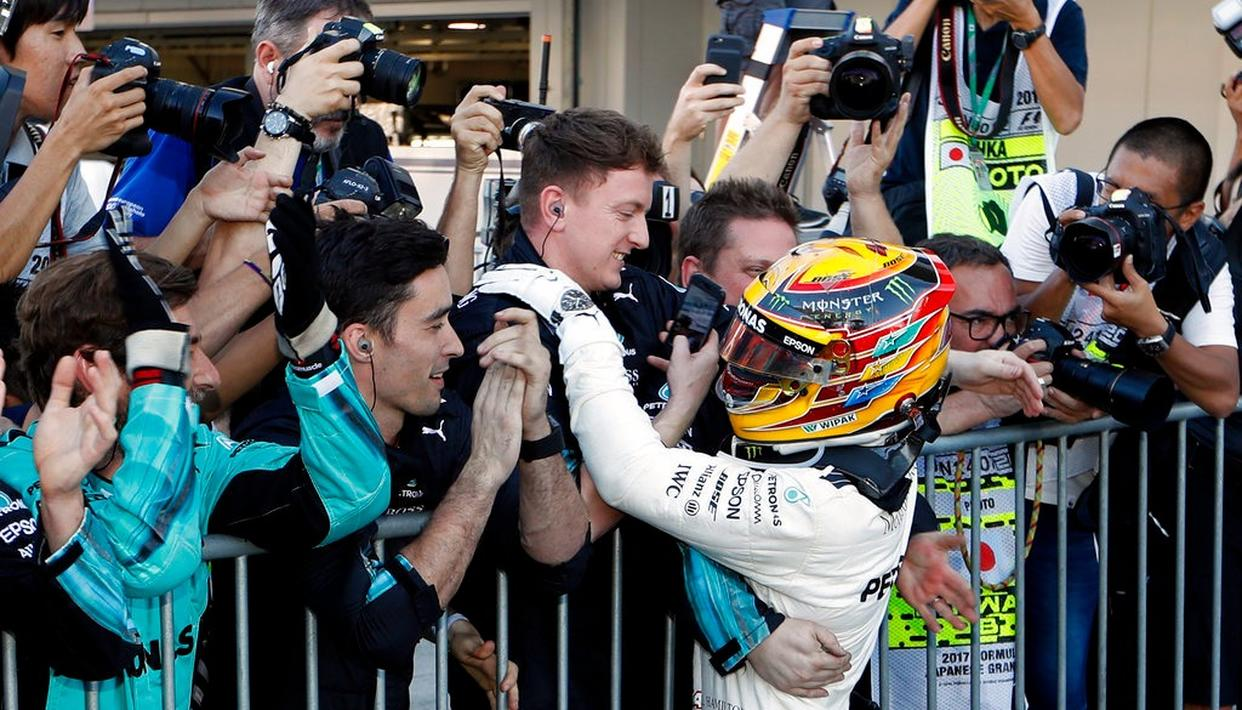 Mercedes driver Lewis Hamilton of Britain is congratulated by his team after winning the Japanese  Grand Prix.