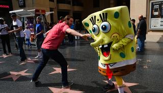 In this photo, Belnarr Golden, wearing a SpongeBob SquarePants costume, dodges a tourist trying to pull the nose of his costume on Hollywood Boulevard, in Los Angeles. (AP)