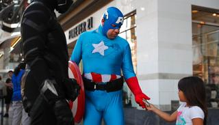 In this photo, a young tourist tips Justin Harrison, wearing a homemade Captain America costume, and Harrison's roommate, Reginald Jackson in a Black Panther costume after taking pictures with them on Hollywood Boulevard in Los Angeles(AP)
