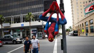 In this photo, Rashad Rouse, 27, whose dream is getting his star on the Hollywood Walk of Fame, hangs upside down from a traffic signal pole in a Spider-Man costume to get attention from tourists on Hollywood Boulevard, in Los Angeles. (AP)