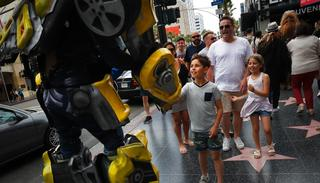 In this photo, Ramiro Rodriguez in a Bumblebee costume, a character from the Transformers movie series, shakes hands with young tourists on Hollywood Boulevard, in Los Angeles. (AP)