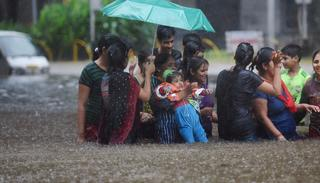 People walk through a flooded street during heavy rains in Mumbai on Tuesday. (PTI Photo)