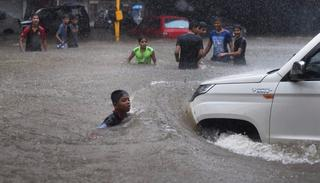 People make their way through a flooded street during heavy rains in Mumbai on Tuesday. (PTI Photo)