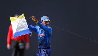Sri Lanka's Akila Dananjaya removes a kite which landed in the ground during the fourth one-day international.
