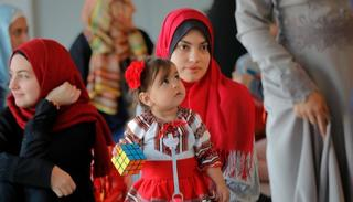 A child holds a toy standing in the women's section before Eid al-Adha prayers, held in a sports hall in Bucharest, Romania. (Source: AP)