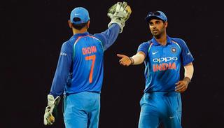 Bhuvneshwar Kumar celebrates with teammate Mahendra Singh Dhoni after his five wicket haul .
