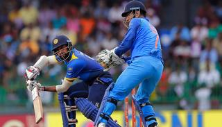 Lahiru Thirimanne, plays a shot as MS Dhoni watches.