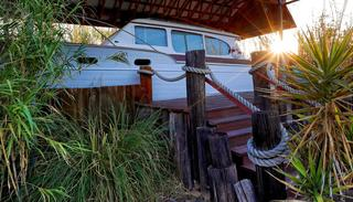 The sun rises behind the stern of a 38-foot 1947 Chris Craft Yacht dry docked at the Shady Dell Trailer Court.