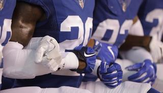 Members of the Indianapolis Colts lock arms as they take a knee during the National Anthem before an NFL football game on Sept. 24