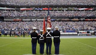 The American flag is presented in front of an empty Tennessee Titans bench area during the playing of the national anthem before an NFL football game between the Titans and the Seattle Seahawks.