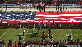 The Pittsburgh Steelers side of the field is nearly empty during the playing of the national anthem before an NFL football game between the Steelers and Chicago Bears.