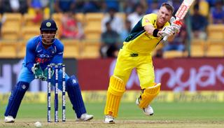 David Warner plays a shot during the fourth ODI as MS Dhoni looks on.