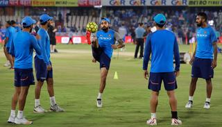 Virat Kohli plays football to warm up before the start of the game.
