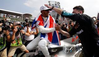 British driver Lewis Hamilton celebrates wining his fourth Formula One championship with a member of his team after the Mexican Formula One Grand Prix.