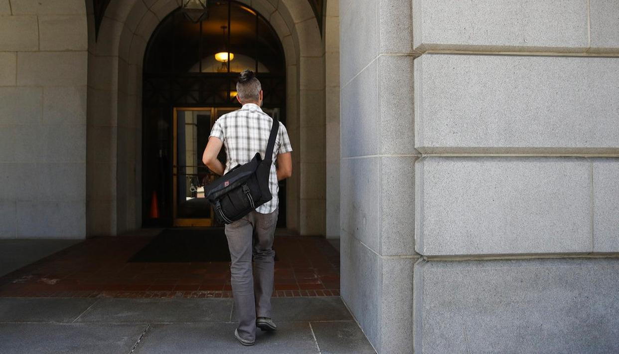 In this June 27, 2017, photo, with $40,131.88 in cash hidden in a shoulder bag, Jerred Kiloh, owner of the Higher Path medical marijuana dispensary, arrives at Los Angeles City Hall to pay his monthly tax in cash in Los Angeles.