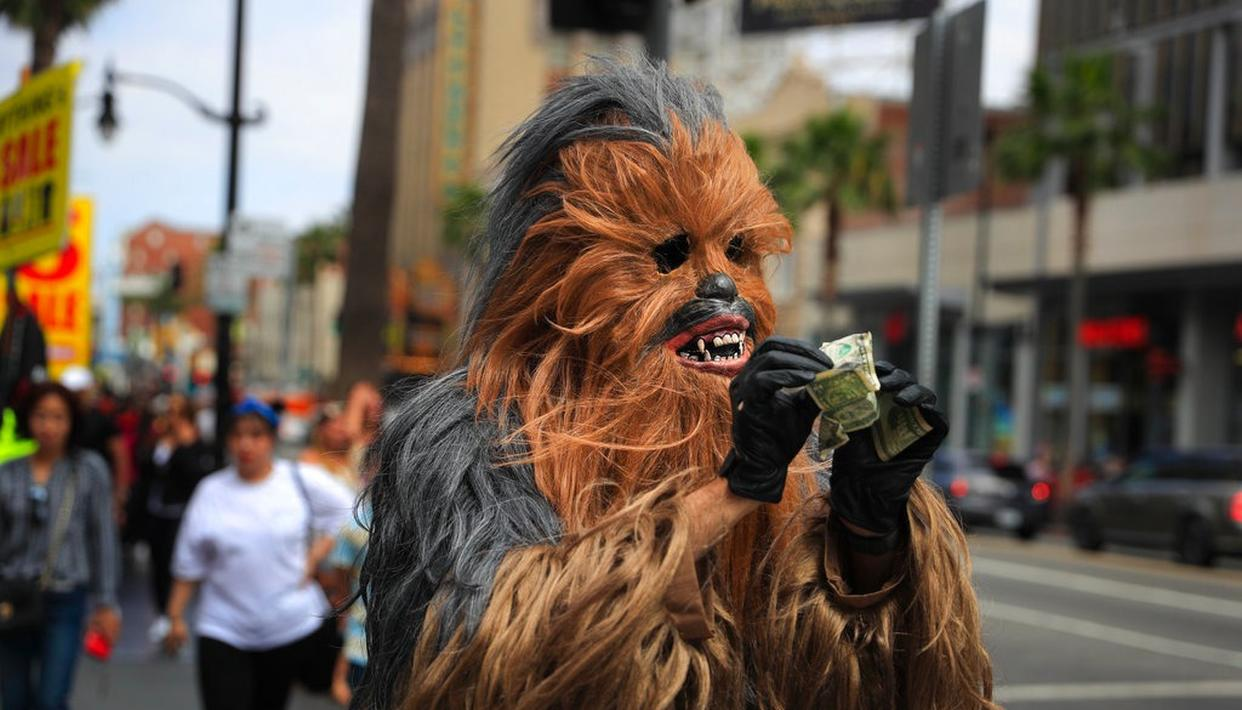 In photo, Donte, a musician who only gave his first name, straightens out dollar bills on his first day in a brand new Chewbacca costume purchased from eBay for $441, in the Hollywood section of Los Angeles.(AP)