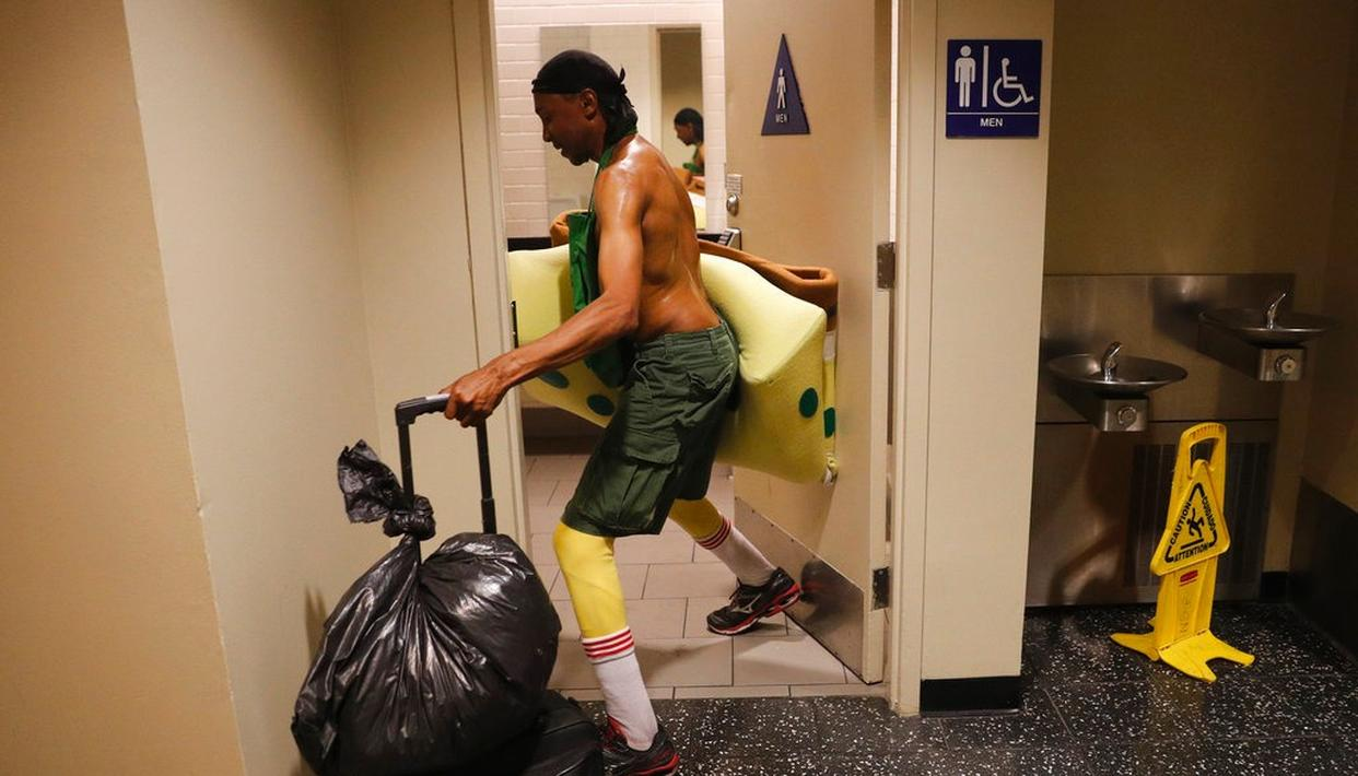 In this photo, covered in sweat, impersonator Belnarr Golden enters a public restroom with his SpongeBob SquarePants costume folded in half after working on Hollywood Boulevard in Los Angeles. (AP)