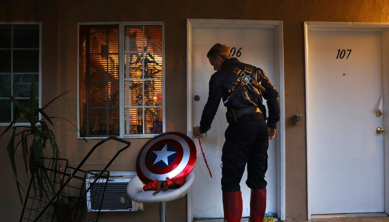 In this photo, Captain America impersonator Henry Hodge, a cinematographer from England who lives a stone's throw away from Hollywood's Dolby Theatre, opens his apartment door in Los Angeles. (AP)