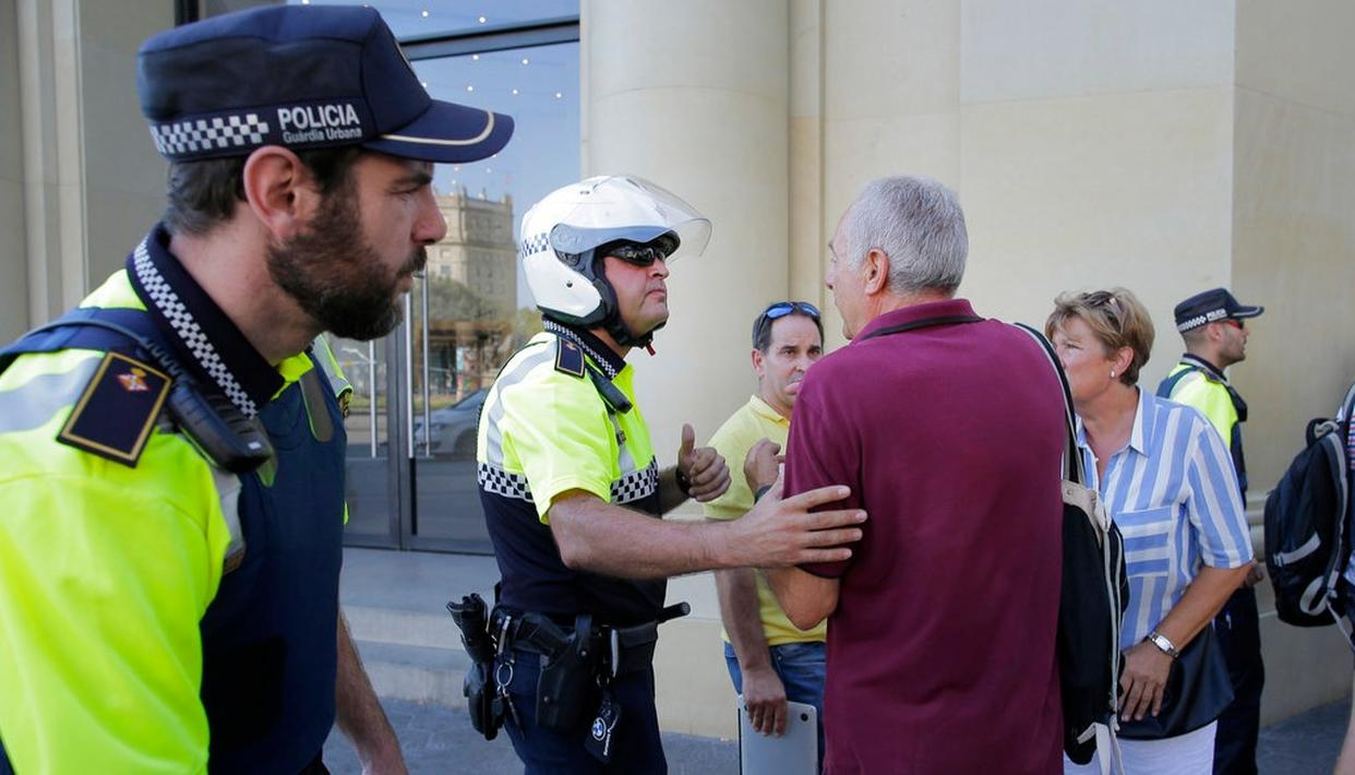Police officers tell members of the public to leave the scene in a street in Barcelona, Spain. (AP Photo)