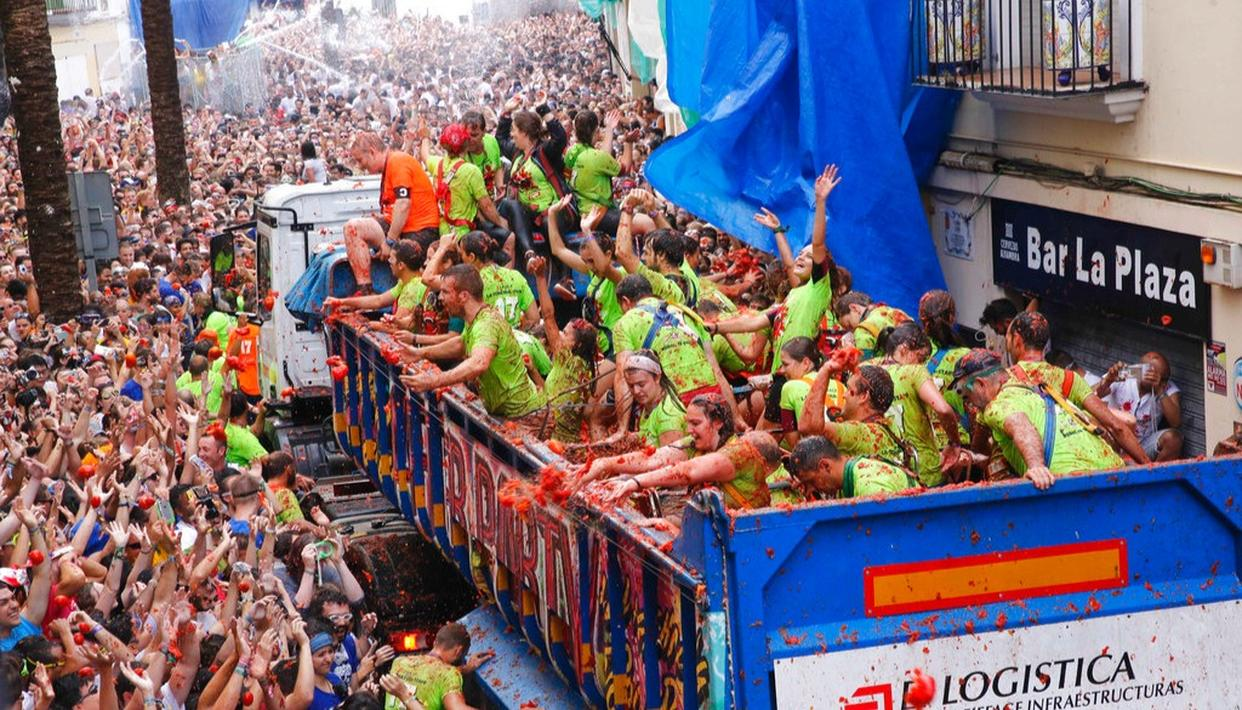 Crowds of people throw tomatoes at each other, during the annual