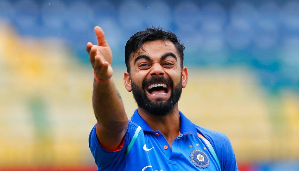 Virat Kohli laughs as he gestures towards a teammate before the start of the fifth .