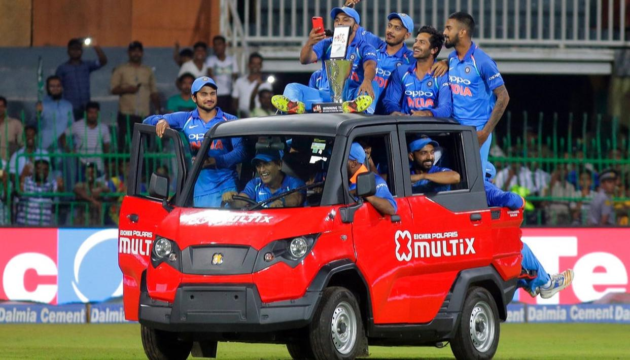 Mahendra Singh Dhoni rides a vehicle carrying fellow team members and the winning trophy after their win over Sri Lanka.