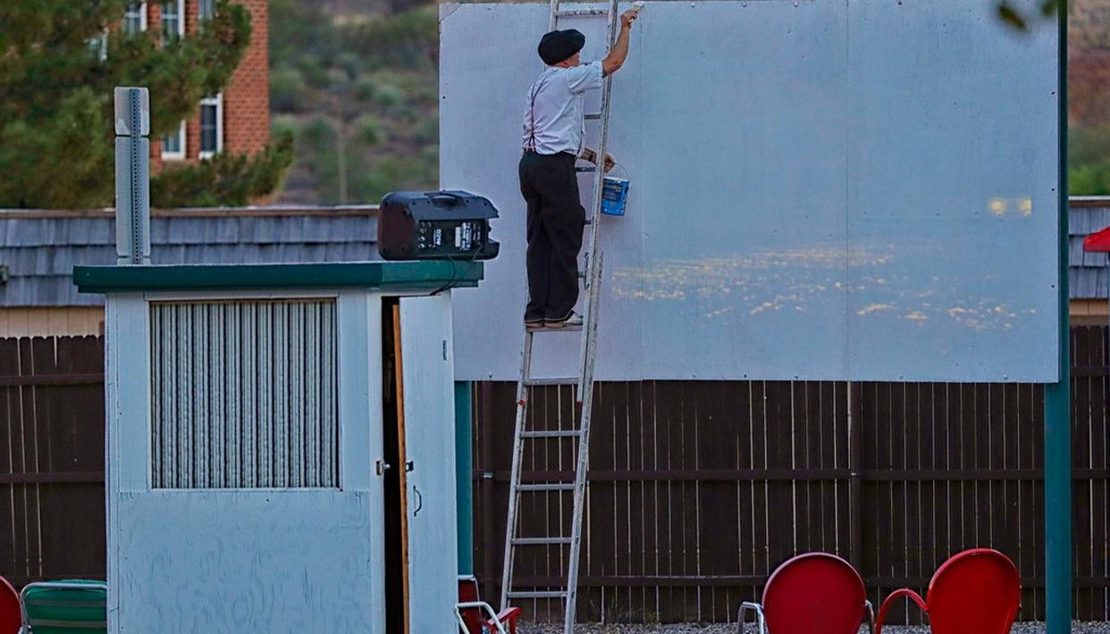 Manager Brad Hardy applies touch up paint to the big screen at the Shady Dell Trailer Court, Tuesday, April 25, 2017, in Bisbee, Ariz.