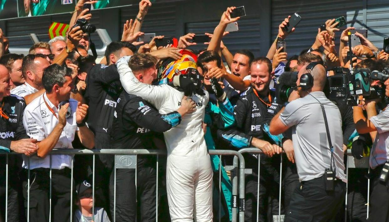 Mercedes driver Lewis Hamilton of Britain celebrates  with the team after winning.