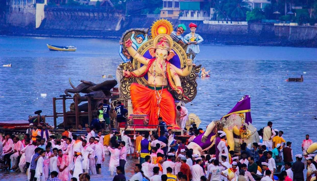 One of the many huge Ganpati statues floating on a wooden raft ready for immersion.