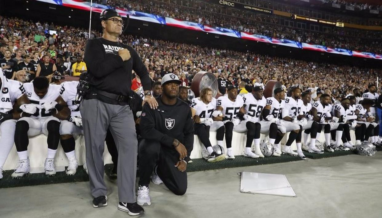 Oakland Raiders kneel during the playing of the National Anthem before an NFL football game against Washington Redskins.