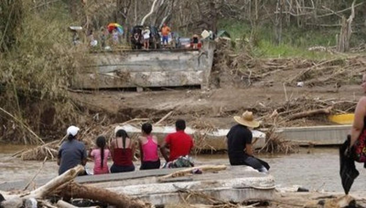 People sit on both sides of a destroyed bridge in the aftermath of Hurricane Maria, in Morovis, Puerto Rico