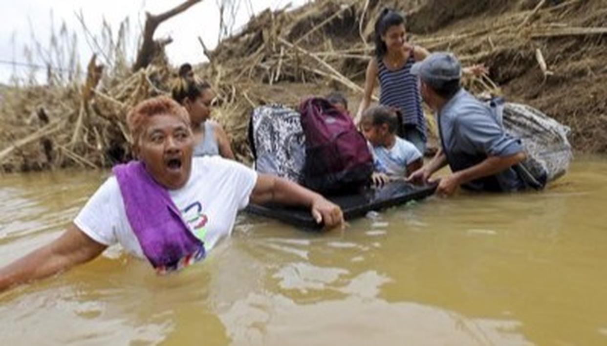 Residents near San Lorenzo Morovis river wade through the waters after the bridge was swept away.