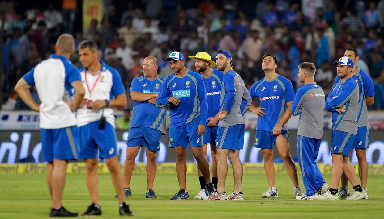 Australian cricketers wait for the start of the match.