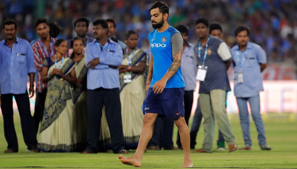 Ground staff watch a barefooted Indian cricket captain Virat Kohli walk past them while teams wait for the outfield to dry.