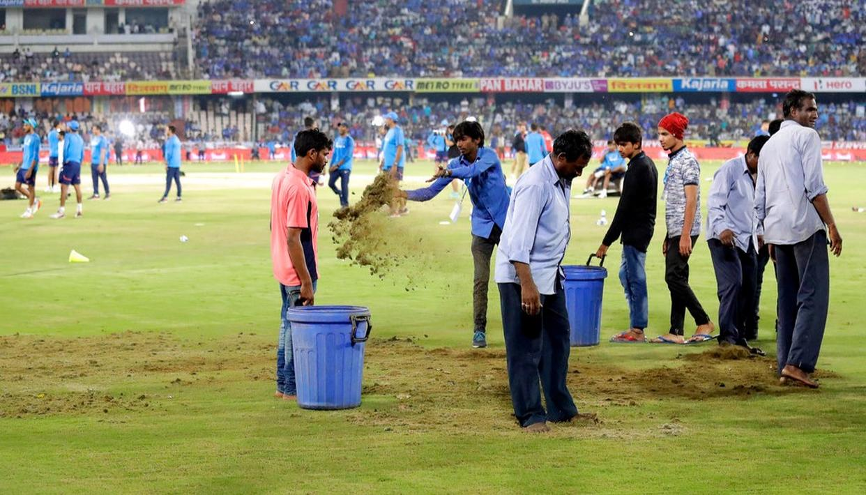 Ground staff work to dry up wet patches before the start of the third T20I.