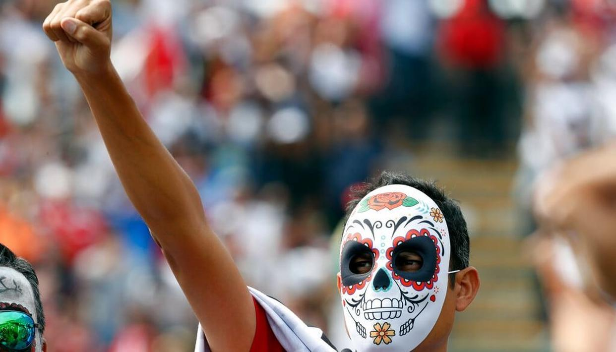 Wearing a Day of the Dead mask a fan holds up his fist honoring earthquake victims during the Formula One Mexico Grand Prix auto race at the Hermanos Rodriguez racetrack in Mexico City.