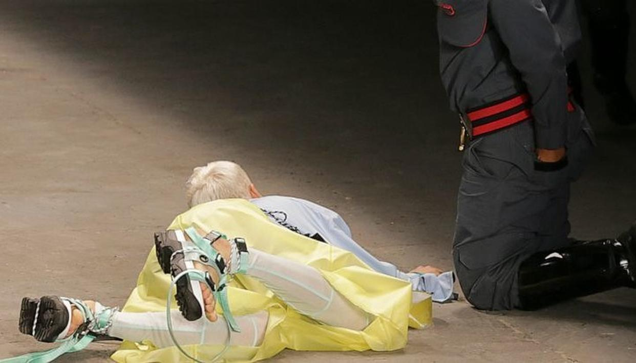 Model Tales Soares lies on the catwalk as a paramedic tends to him after he collapsed during Sao Paulo Fashion Week (AP)
