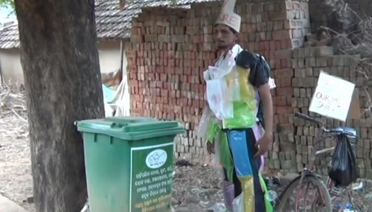 THIS MAN DRESSED IN COLOURFUL POLYTHENE HAS A MESSAGE TO CONVEY